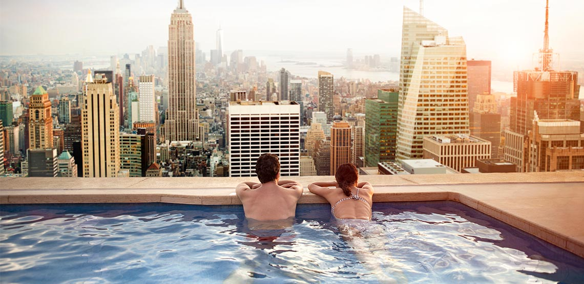 Couple looking out over city from rooftop pool.
