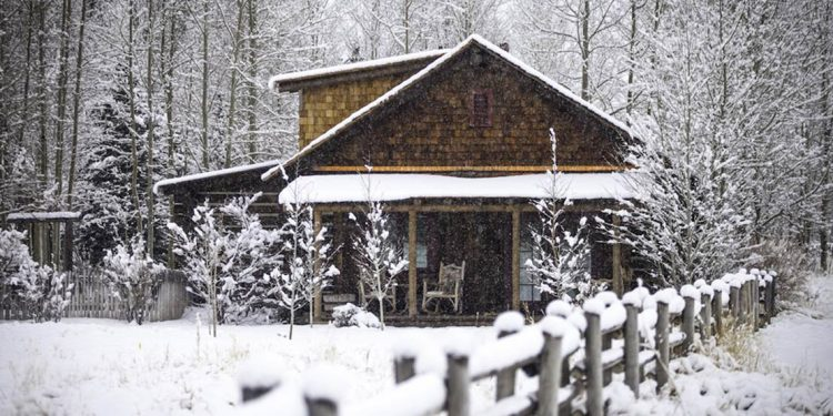 Cabin covered in snow.