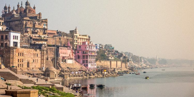 Cityscape of Varanasi with Ganges River in foreground.