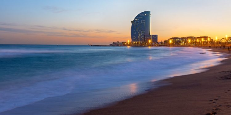 The beach of Barcelona with a modern skyscraper at sunset