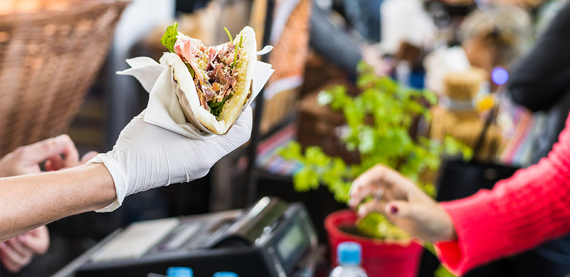 Gloved hand handing tortilla to someone at an outdoor food stall