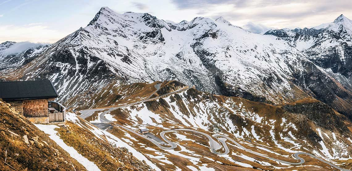 Winding road up mountainside with snow covered peaks