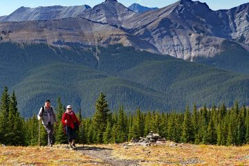 Two people hiking on trail with mountains in background.