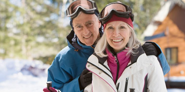 Two older adults in ski gear.