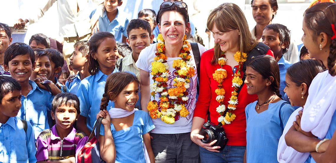Tourists wearing flowers garlands on their necks stand among a group of school girls in India
