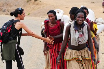 A tourist in Ethiopia greets local villagers with a culturally correct handshake