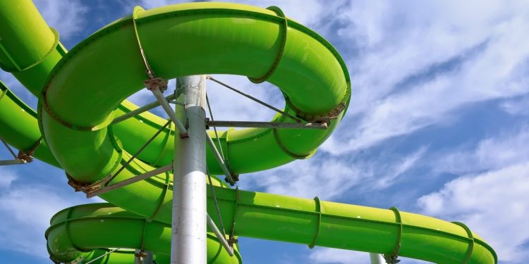 Green water park pipes against a blue sky