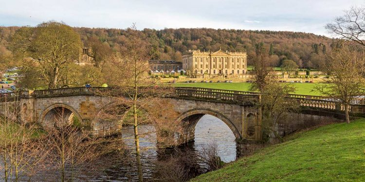 Bridge over river with Chatsworth House in the background.