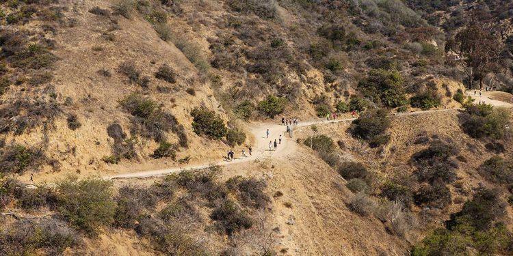 People walking along path cut into side of hill.