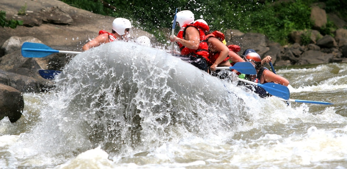 Boatload of rafters splashing through rapids on the New River