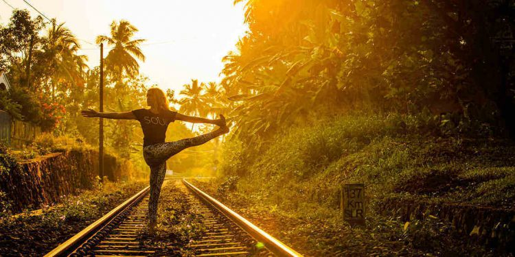 Sunrise yoga practise on train track in tropical sri lanka.
