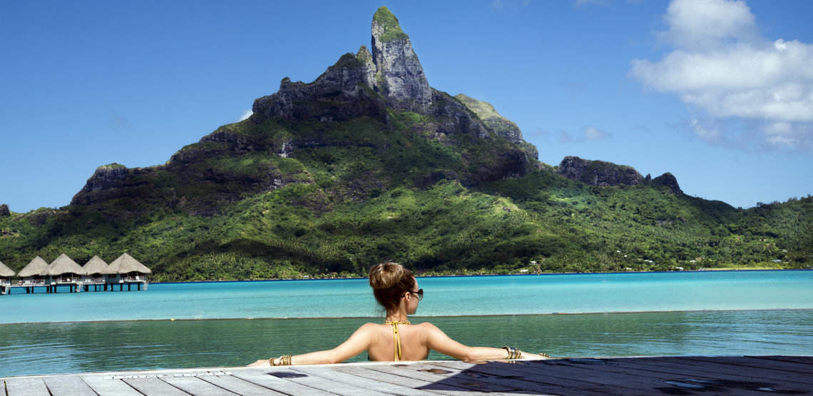 woman in infinity pool of a luxury vacation resort in the lagoon and looking on the Otemanu mountain on Bora Bora