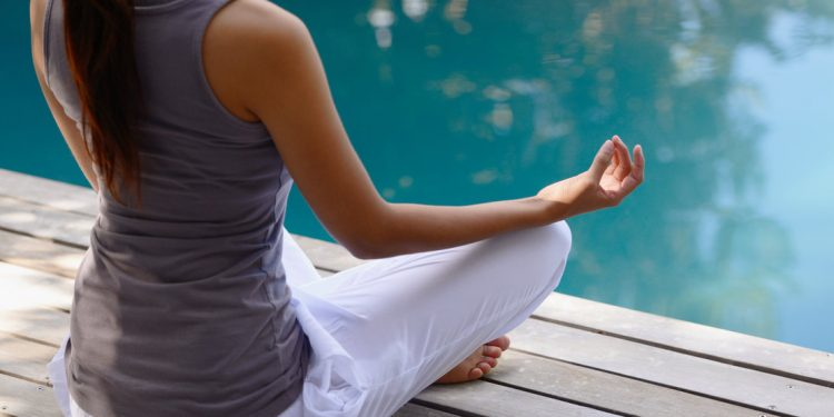 A relaxed young woman meditating next to a pool