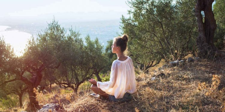 woman in olive field meditating on island in greece at sunset