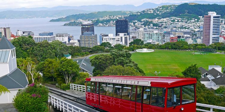 A bright red Wellington cable car moves down its track with the city in the background