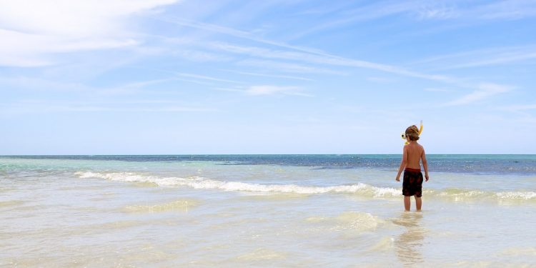Little boy standing in ocean with snorkel mask on