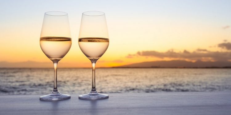 A pair of wine glasses on the beach