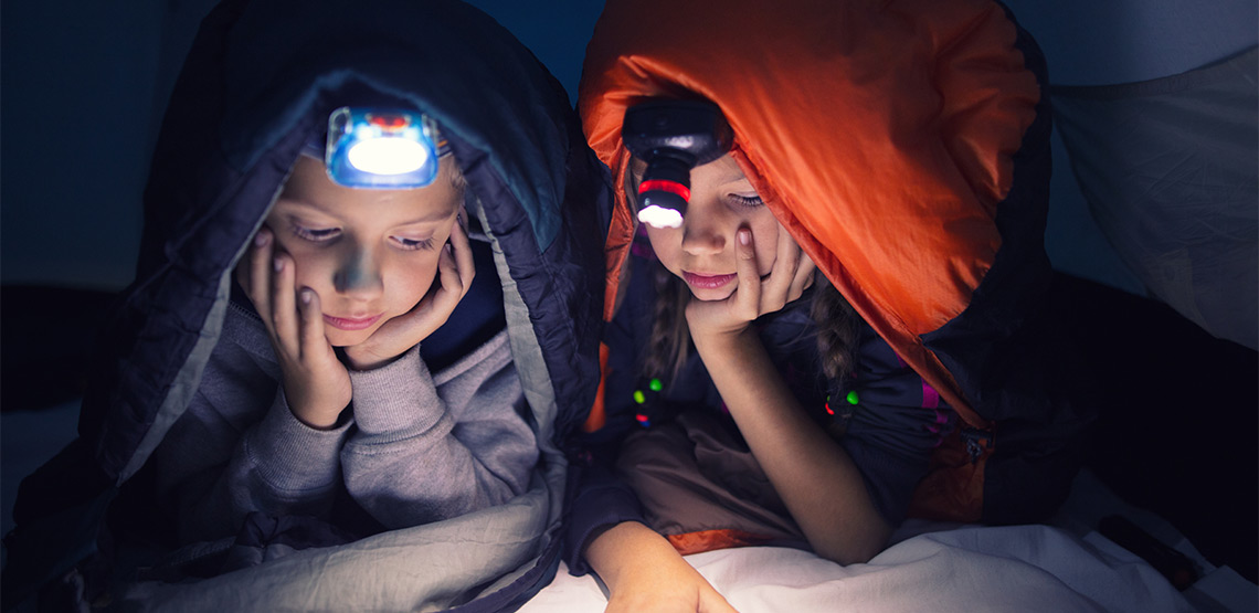 Two kids reading by headlamp in a tent.