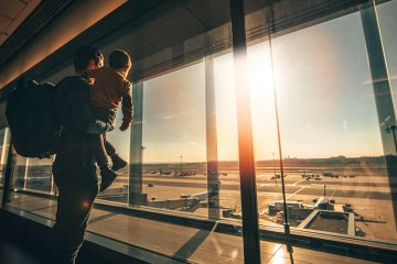 Father and child standing in airport looking out window at planes.