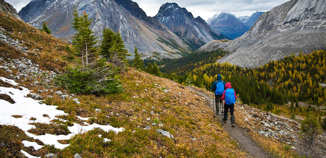 Two people hiking on trail in mountains