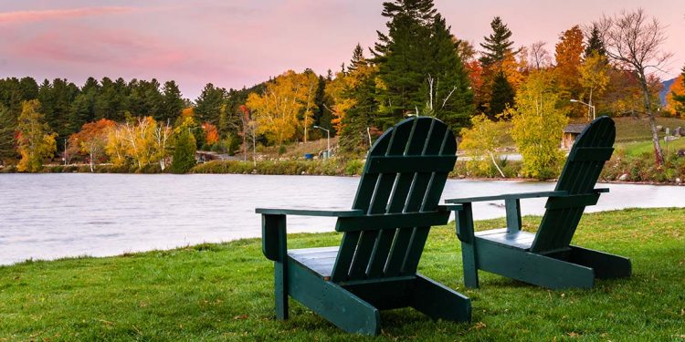 Two Adirondack chairs on Lake Placid in the fall.