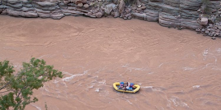 Raft on Colorado River going through Grand Canyon