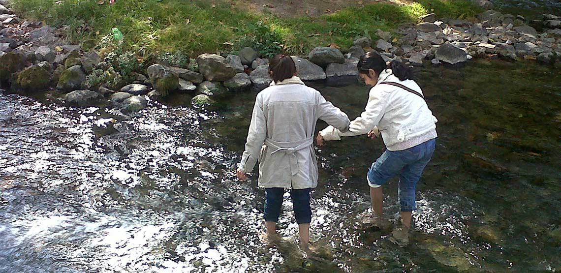 Two girls wading in river.