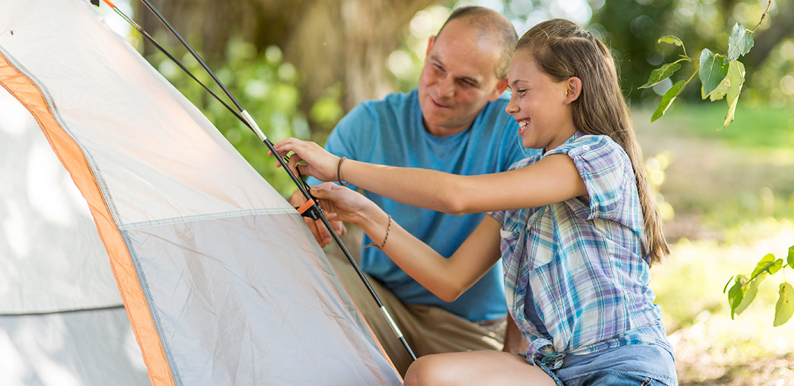 Father and daughter setting up tent.