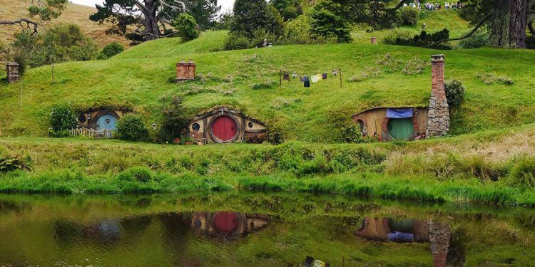 Thre hobbit holes in hillside in Hobbiton