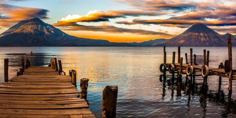 Pier extending into water with mountains in background.