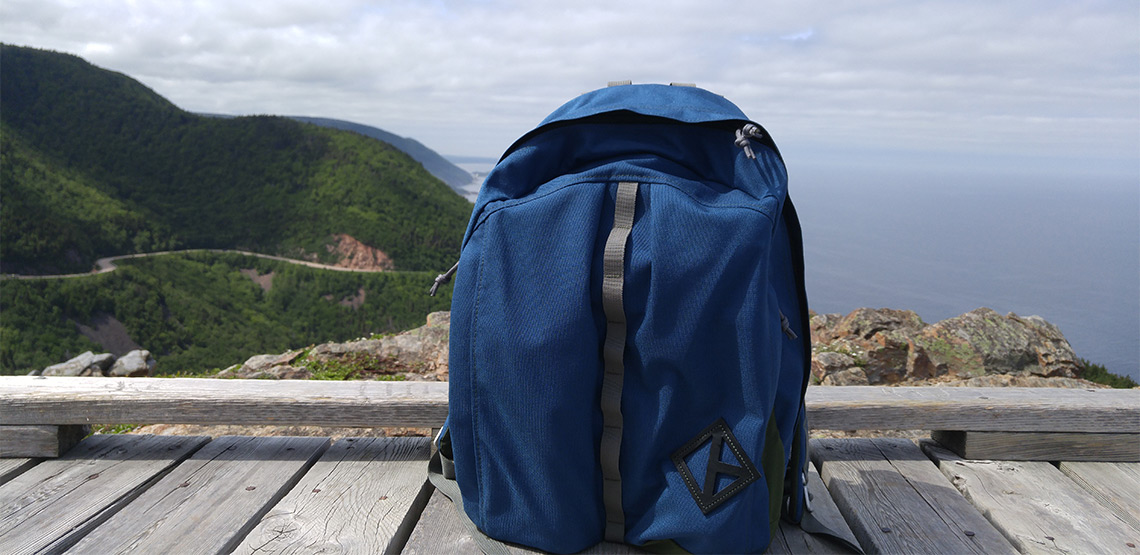 Backpack sitting on boardwalk with Cabot Trail in background