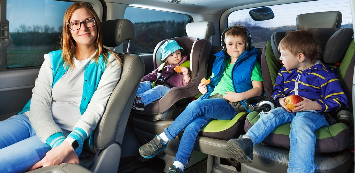 Portrait of mother and three boys sitting in a car