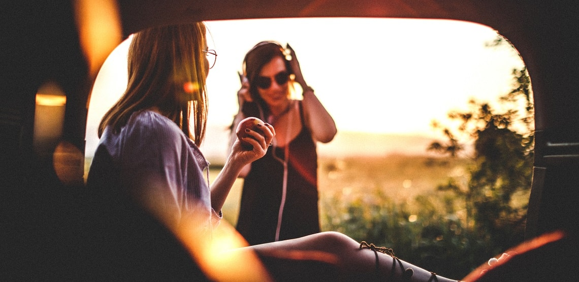 A pair of women on a road trip enjoy an apple and music