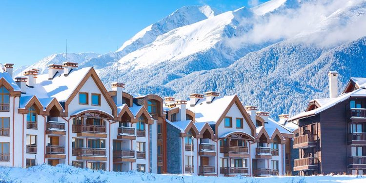 Chalets with mountain in background in wintertime