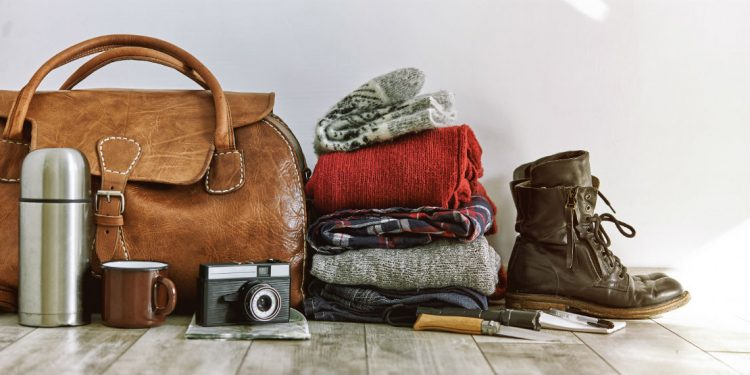 A selection of hiking gear including boots, a camera, and drinkbottle.