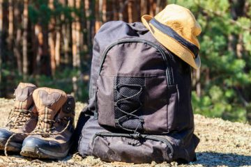 Hiking boots and a backpack resting on the ground in the woods.