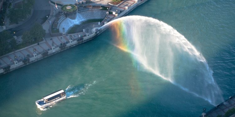 A boat passing by centennial fountain on the chicago river