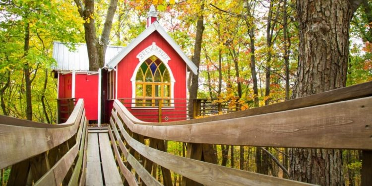 Red treehouse with boardwalk leading to door