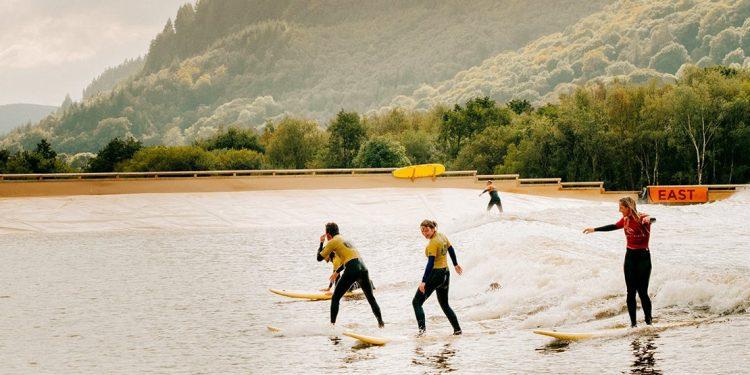 Four people surfing on man made lake
