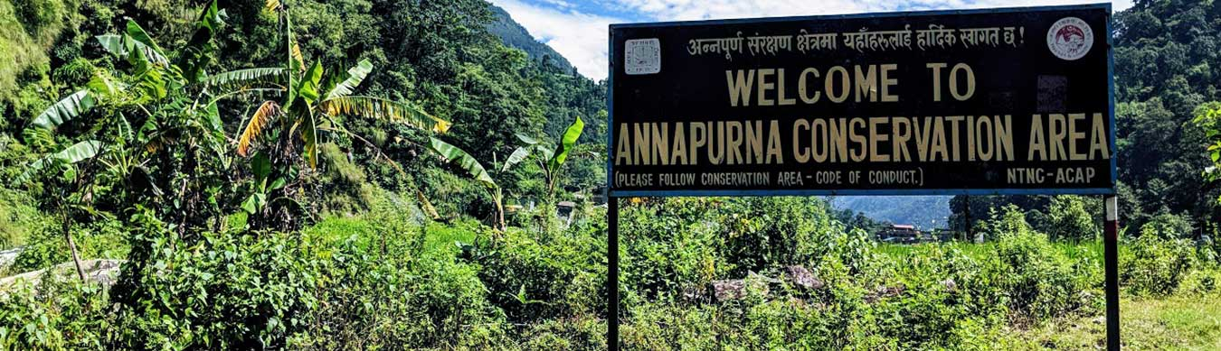 "Sign reading ""welcome to Annapurna Conservation Area"" with jungle in background"