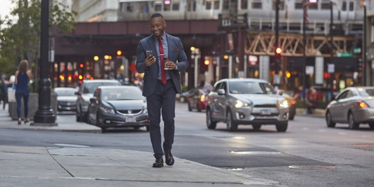 A smiling man using a smart phone while walking on a city street