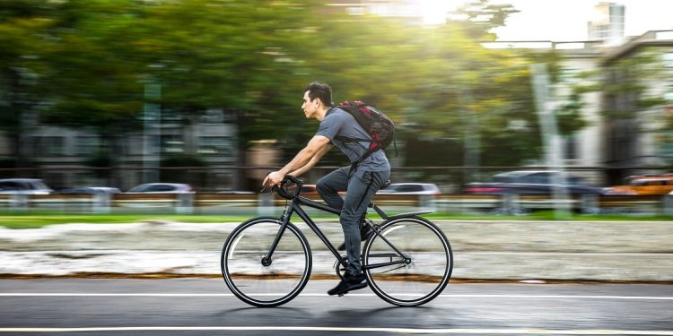 A young man cycling in Chicago, the background blurred by his speed