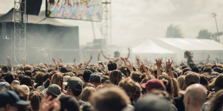 A crowd at a music festival, arms thrust into the air as revelers stand before a stage