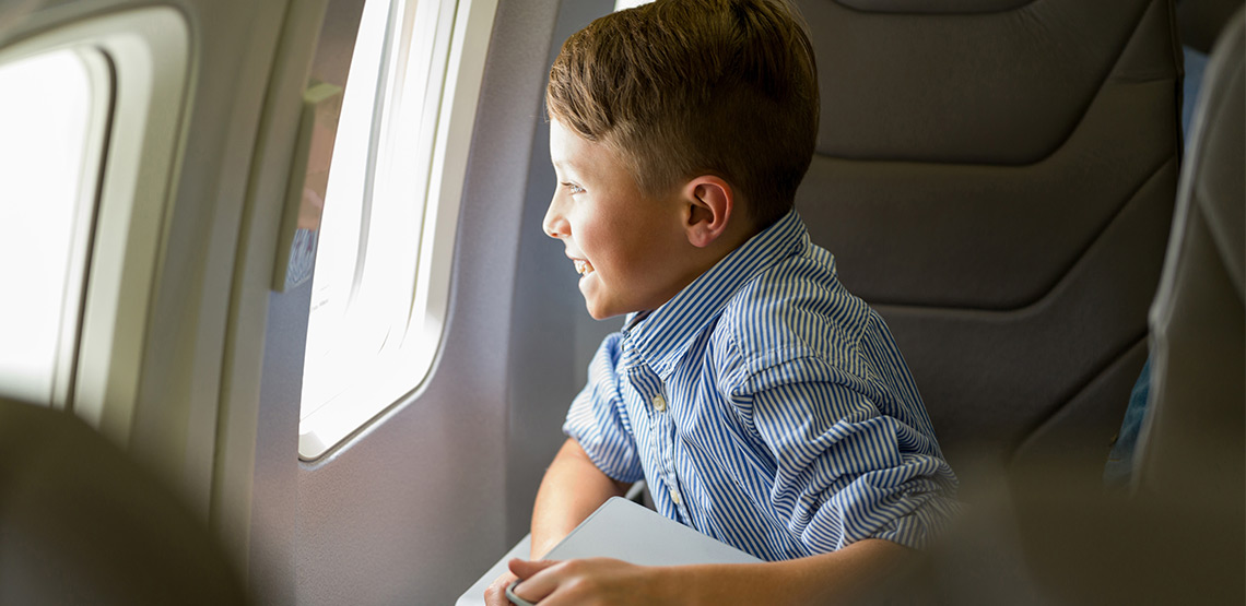 Boy excitedly staring out plane window