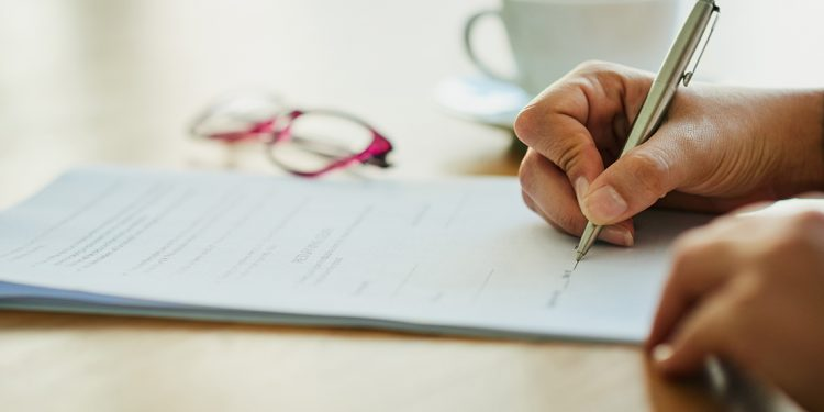 Someone signing a contract with glasses and a mug in the background