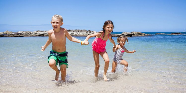 Three kids running out of the water, holding hands