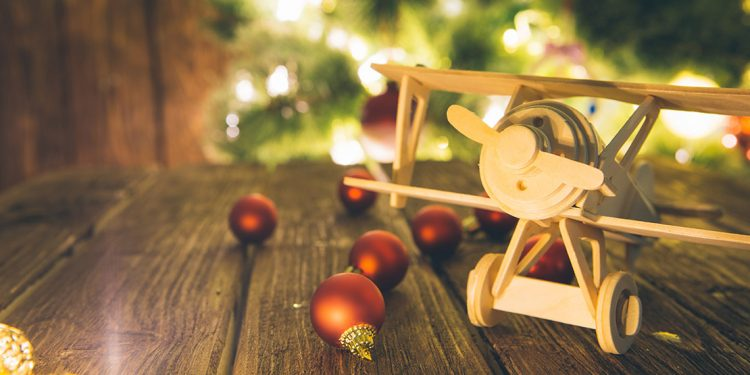 Toy plane with Christmas ornaments and Christmas tree in background