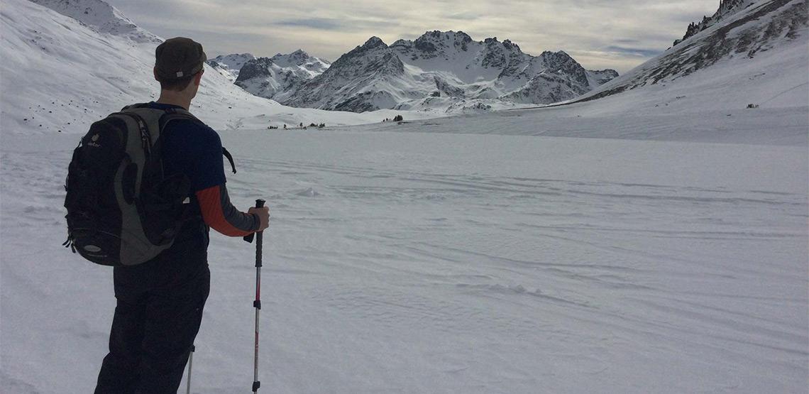 Snowshoer looking out across mountain range