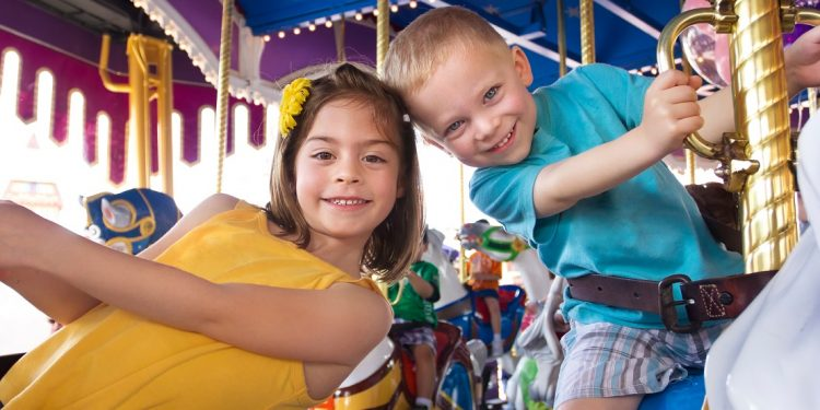Two cute kids having fun while riding a carousel at an amusement park or carnival