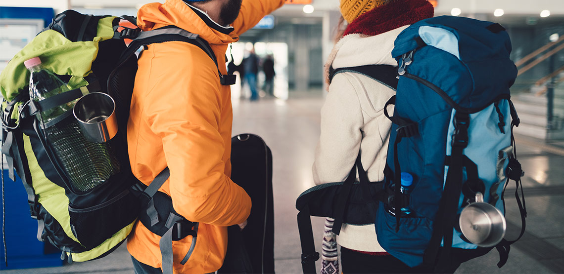 Two people in airport with backpacks
